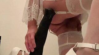 Ladyboy in white lingerie riding big black dildo